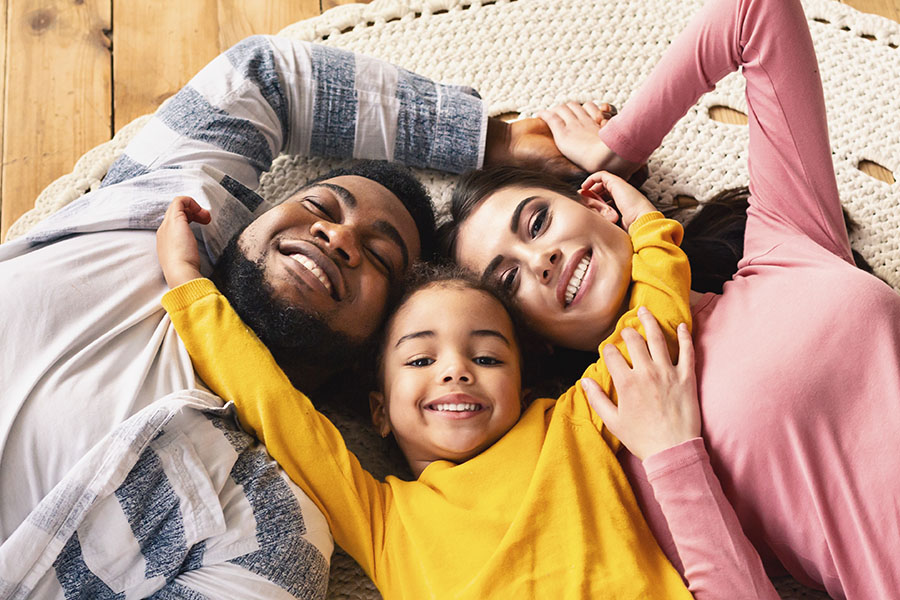 Personal Insurance - Smiling Family Laying On Floor In Their Home